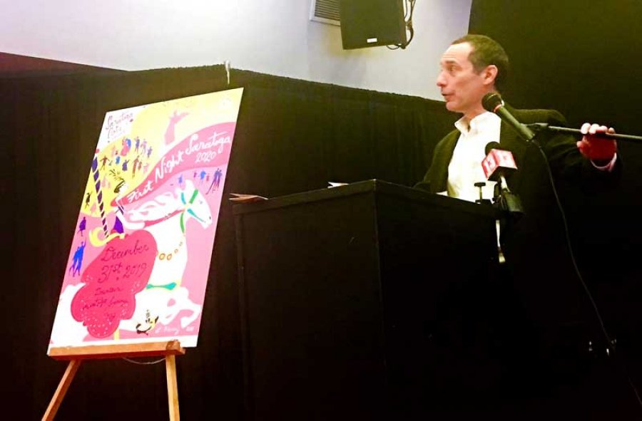 Joel Reed, executive director of Saratoga Arts, unveils First Night 2020 poster. Photo by Thomas Dimopoulos.